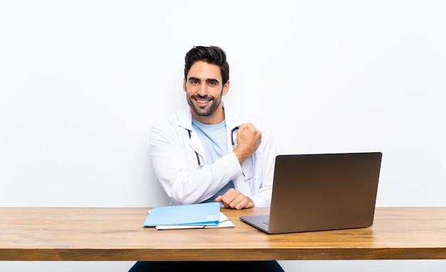 Homem jovem médico com seu laptop sobre parede isolada, celebrando uma vitória Foto Premium