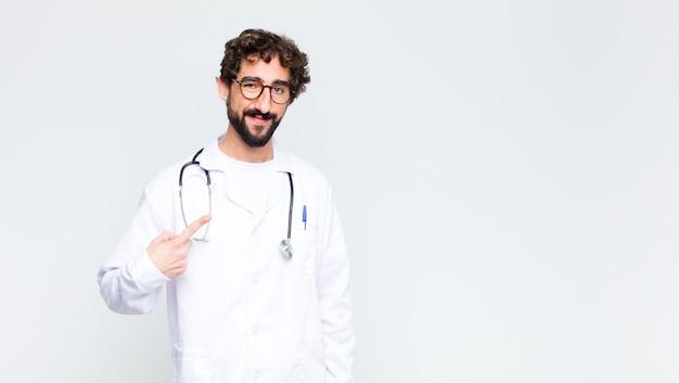 Homem jovem médico olhando orgulhoso, confiante e feliz, sorrindo e apontando para si mesmo ou fazendo o sinal número um contra a parede do espaço de cópia Foto Premium