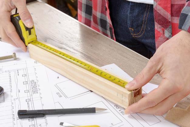 Homem jovem, medindo, tábua madeira Foto Premium