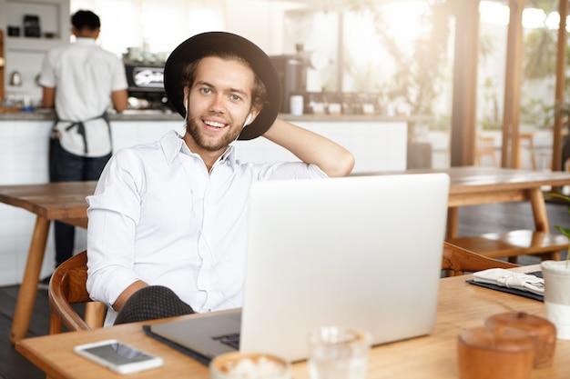 Homem jovem moderno em chapéus da moda se divertindo sozinho, aproveitando o tempo de lazer em um café, navegando na internet, usando wi-fi gratuito no laptop, ouvindo música online em fones de ouvido Foto gratuita
