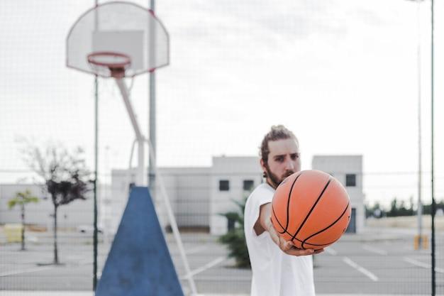 Homem jovem, mostrando, basquetebol, em, corte Foto gratuita