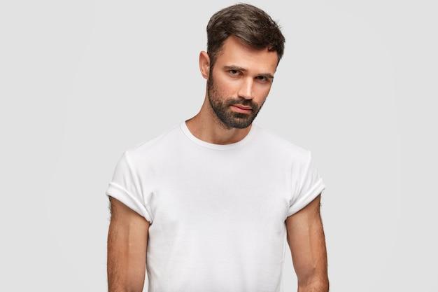 Homem jovem musculoso sério com restolho escuro, cabelo, vestido com uma camiseta branca casual, tem corpo musculoso, ouve algo com atenção, isolado sobre uma parede branca. cara com a barba por fazer fica dentro de casa Foto gratuita