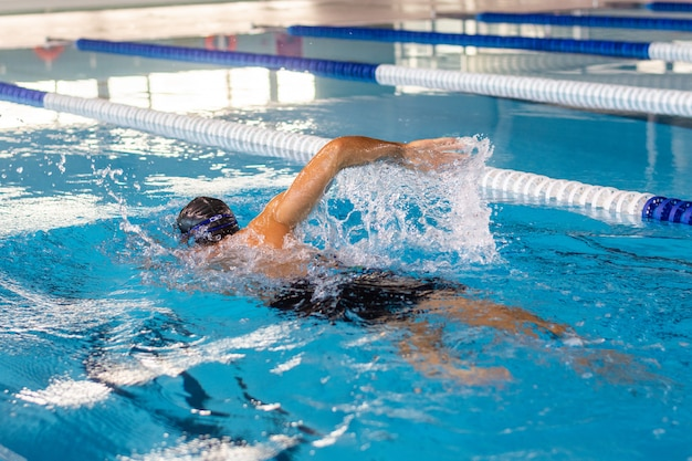 Homem jovem nadador nadar na piscina olímpica Foto Premium