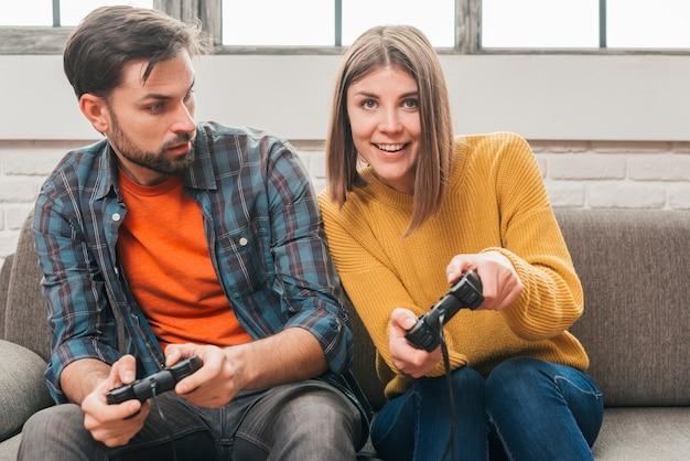 Homem jovem, olhar, dela, namorada, jogando videogame, com, joystick Foto gratuita
