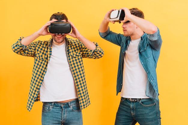 Homem jovem, olhar, seu, amigo, desfrutando, a, realidade virtual, óculos, contra, amarela, fundo Foto gratuita