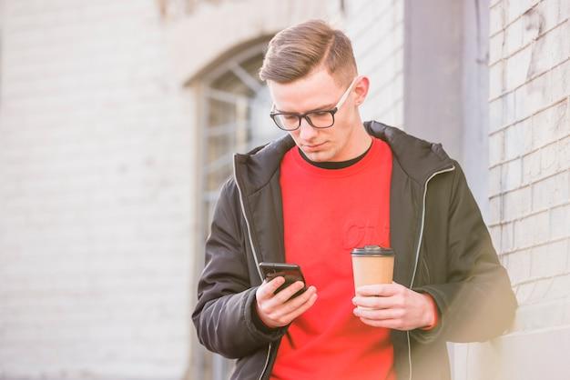 Homem jovem, olhar, telefone móvel, segurando, copo café descartável, em, mão Foto gratuita