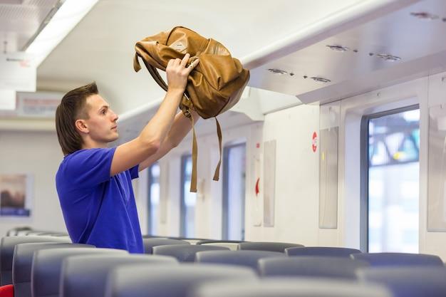 Homem jovem, pôr, bagagem, em, despesas gerais, locker, em, trem Foto Premium