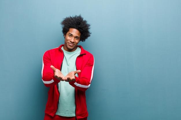 Homem jovem preto esportes sorrindo alegremente com olhar amigável, confiante e positivo, oferecendo e mostrando um objeto ou conceito contra grunge Foto Premium