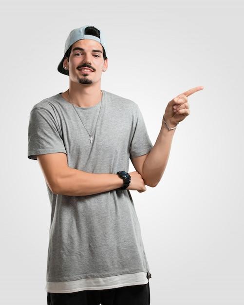 Homem jovem rapper apontando para o lado, sorrindo surpreso apresentando algo, natural e casual Foto Premium