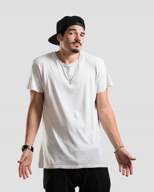 Homem jovem rapper duvidando e encolhendo os ombros, conceito de indecisão e insegurança, incerto sobre algo Foto Premium