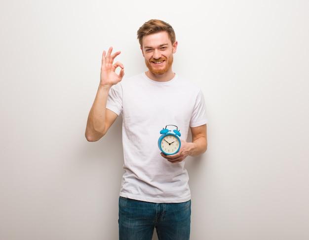 Homem jovem ruiva alegre e confiante, fazendo o gesto de ok. ele está segurando um despertador. Foto Premium