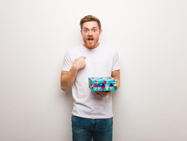 Homem jovem ruiva surpreso, sente-se bem sucedido e próspero. segurando uma caixa de presente. Foto Premium