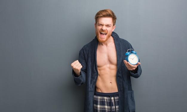 Homem jovem ruiva vestindo pijama surpreso e chocado. ele está segurando um despertador. Foto Premium