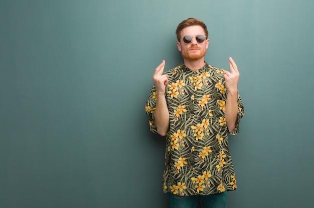 Homem jovem ruiva vestindo roupas de verão exóticas, cruzando os dedos por ter sorte Foto Premium