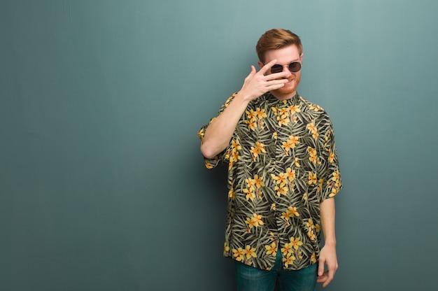 Homem jovem ruiva vestindo roupas de verão exóticas envergonhado e rindo ao mesmo tempo Foto Premium