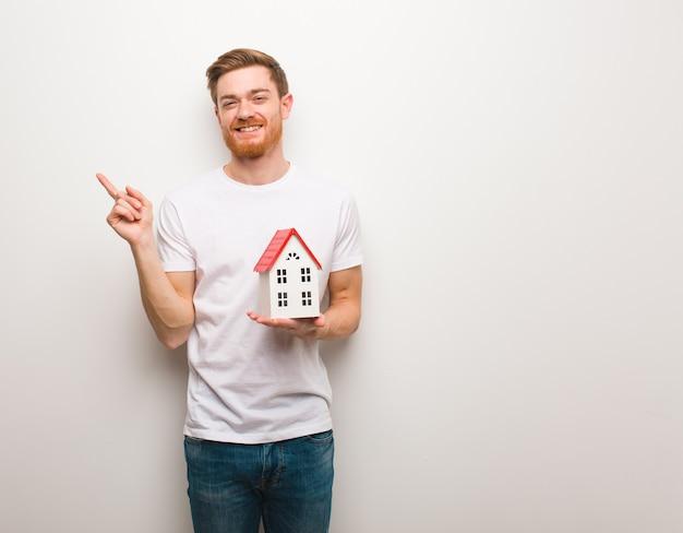 Homem jovem ruivo apontando para o lado com o dedo. segurando um modelo de casa. Foto Premium