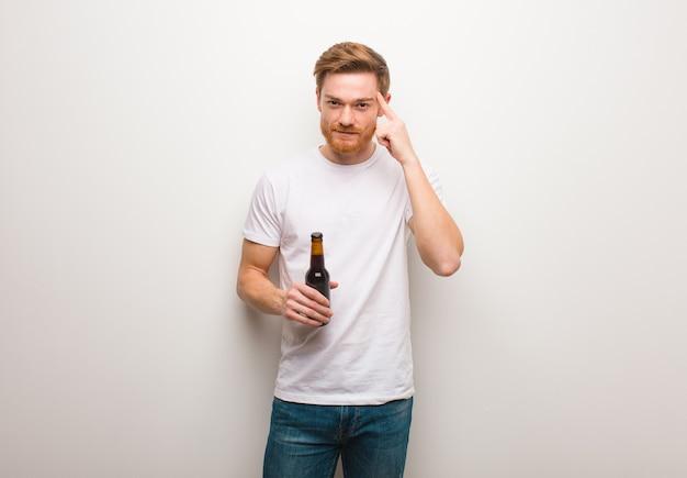 Homem jovem ruivo pensando em uma ideia. segurando uma cerveja. Foto Premium