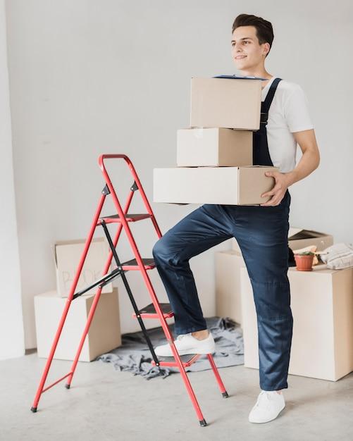 Homem jovem, segurando, caixas, com, pé, ligado, escada Foto gratuita