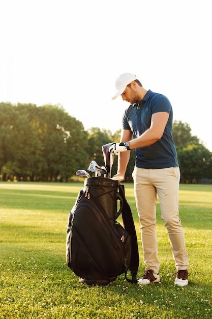 Homem jovem, segurando clube golfe Foto gratuita