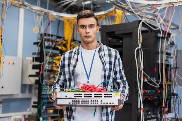 Homem jovem, segurando, ethernet, interruptores Foto gratuita