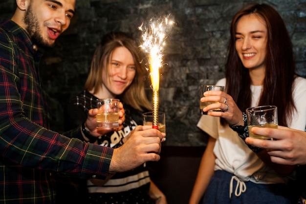 Homem jovem, segurando, iluminado, faísca, celebrando, com, amigos Foto gratuita