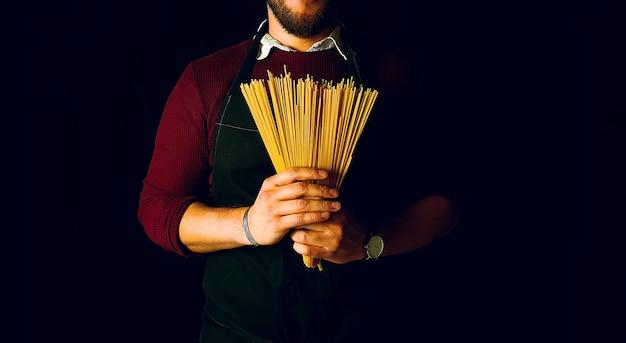 Homem jovem, segurando, macarrão espaguete, com, avental Foto Premium
