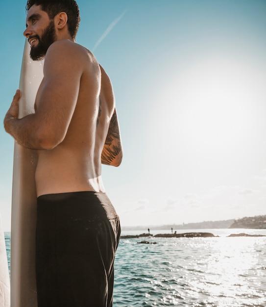 Homem jovem, segurando, prancha surf, frente, perto, oceânicos Foto gratuita