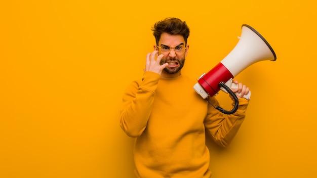 Homem jovem, segurando, um, megafone, zangado, e, virada Foto Premium