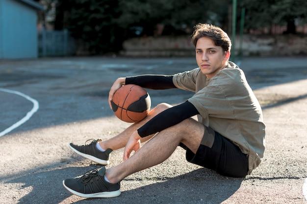 Homem jovem, sentando, ligado, quadra basquetebol Foto gratuita