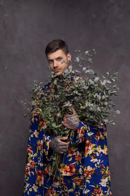 Homem jovem sério com tatuagem na mão segurando galhos de planta Foto gratuita