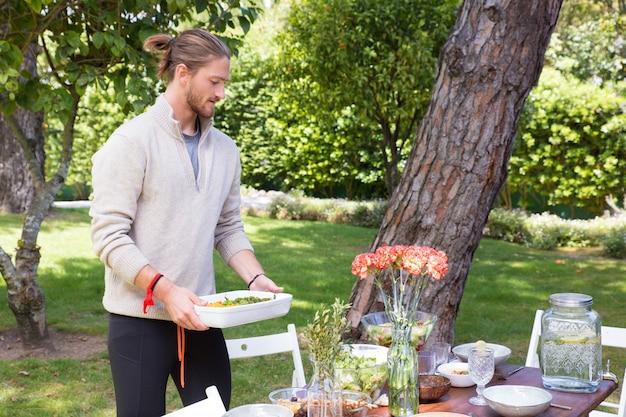 Homem jovem sério servindo refeição ao ar livre Foto gratuita