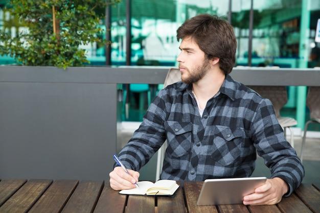 Homem jovem sério usando aplicativo financeiro Foto gratuita