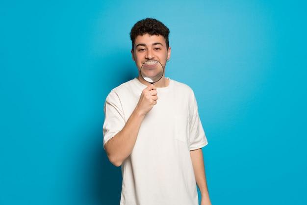 Homem jovem, sobre, azul, levando, um, lupa, e, mostrando, dentes, através Foto Premium