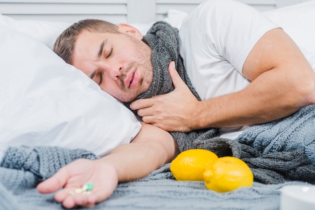 Homem jovem, sofrimento, de, frio, encontrar-se cama, com, pílulas, em, seu, mão Foto gratuita