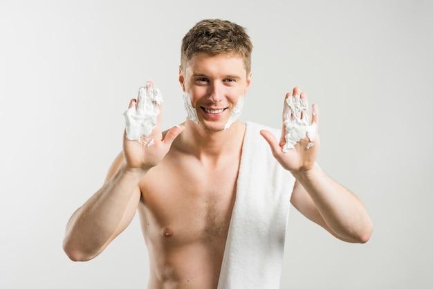Homem jovem sorridente sem camisa, mostrando a espuma de barbear nas palmas das mãos contra o fundo cinza Foto gratuita