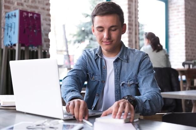Homem jovem, tabela, com, laptop Foto gratuita