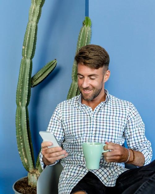Homem jovem, tendo um café Foto gratuita