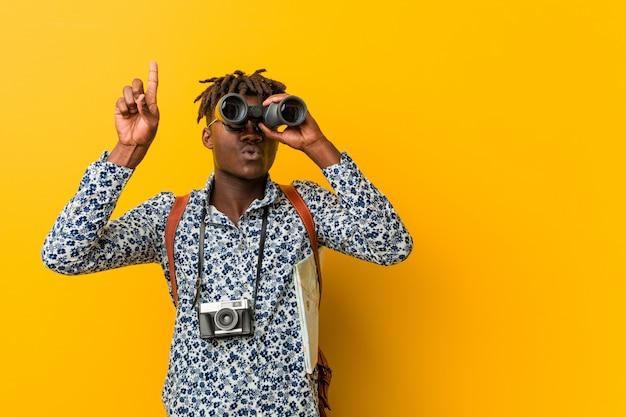 Homem jovem turista africano em pé segurando um binóculo amarelo Foto Premium