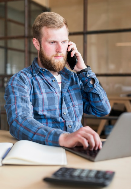 Homem jovem, usando, cellphone, enquanto, trabalhando, laptop, em, escritório Foto gratuita