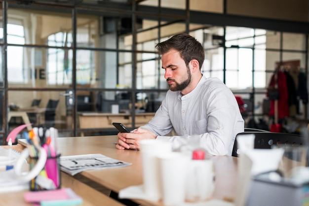Homem jovem, usando, smartphone, sentando, em, escritório Foto gratuita