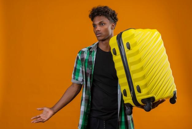 Homem jovem viajante afro-americano segurando uma mala, olhando de lado, confuso, sem ter resposta, em pé sobre um fundo laranja Foto gratuita