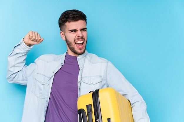 Homem jovem viajante caucasiano segurando uma mala isolada, levantando o punho após uma vitória, o conceito de vencedor. Foto Premium