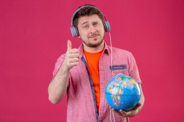 Homem jovem viajante com fones de ouvido, ouvindo música, segurando um globo, mostrando os polegares para cima, sorrindo em pé sobre um fundo rosa Foto gratuita