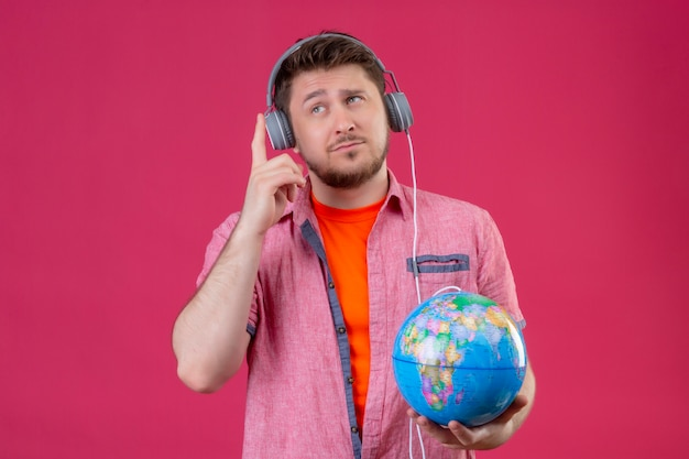 Homem jovem viajante com fones de ouvido segurando um globo, ouvindo música, sorrindo positivamente em pé sobre o fundo rosa Foto gratuita