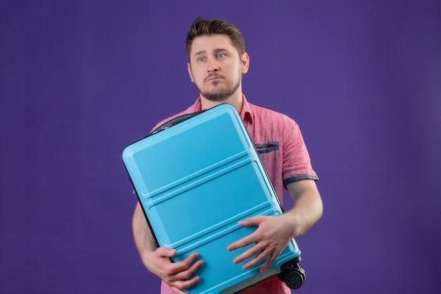 Homem jovem viajante descontente segurando uma mala azul olhando para o lado com uma expressão triste Foto gratuita
