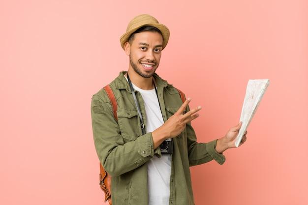 Homem jovem viajante segurando um mapa Foto Premium