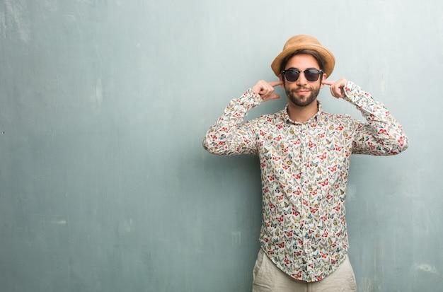 Homem jovem viajante vestindo uma camisa colorida, cobrindo as orelhas com as mãos Foto Premium
