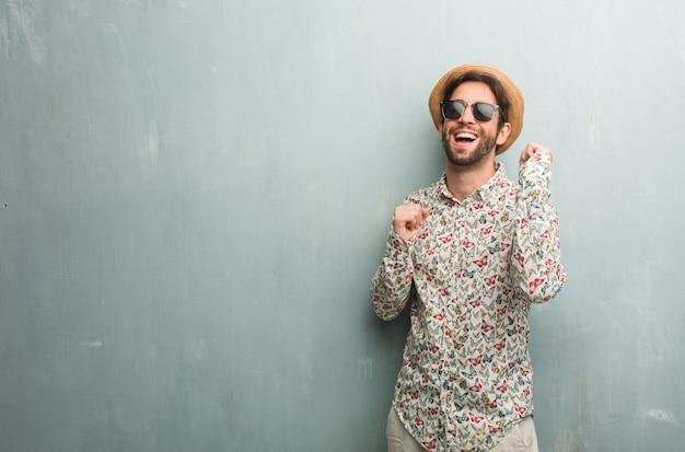 Homem jovem viajante vestindo uma camisa colorida, ouvir música, dançar e se divertir Foto Premium