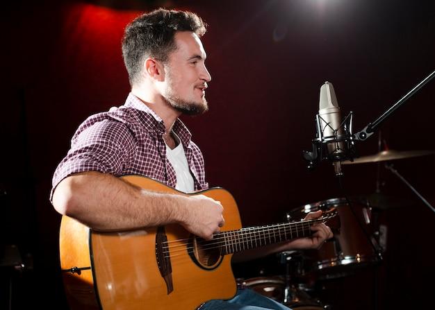 Homem lateral tocando violão e olhando para o microfone Foto gratuita