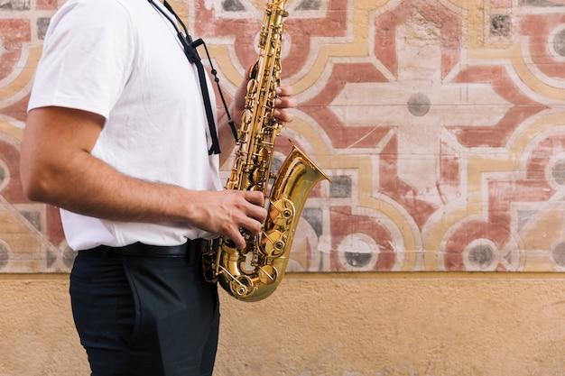 Homem, lateralmente, tocando, saxofone, com, geométrico, fundo Foto gratuita